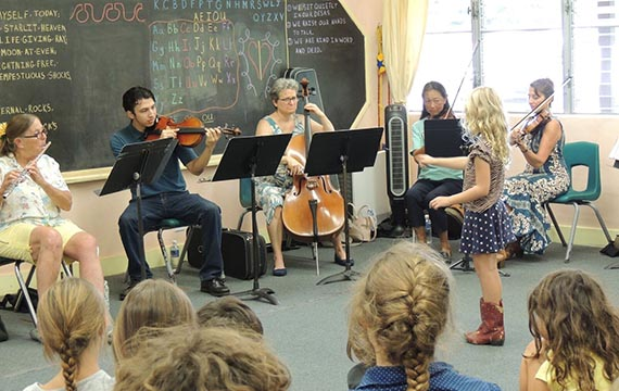 Members of the orchestra performing in front a student audience