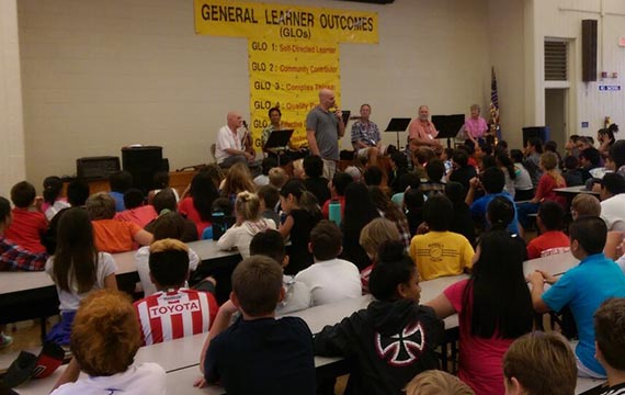 Brian speaking to students in attendance at a school performance