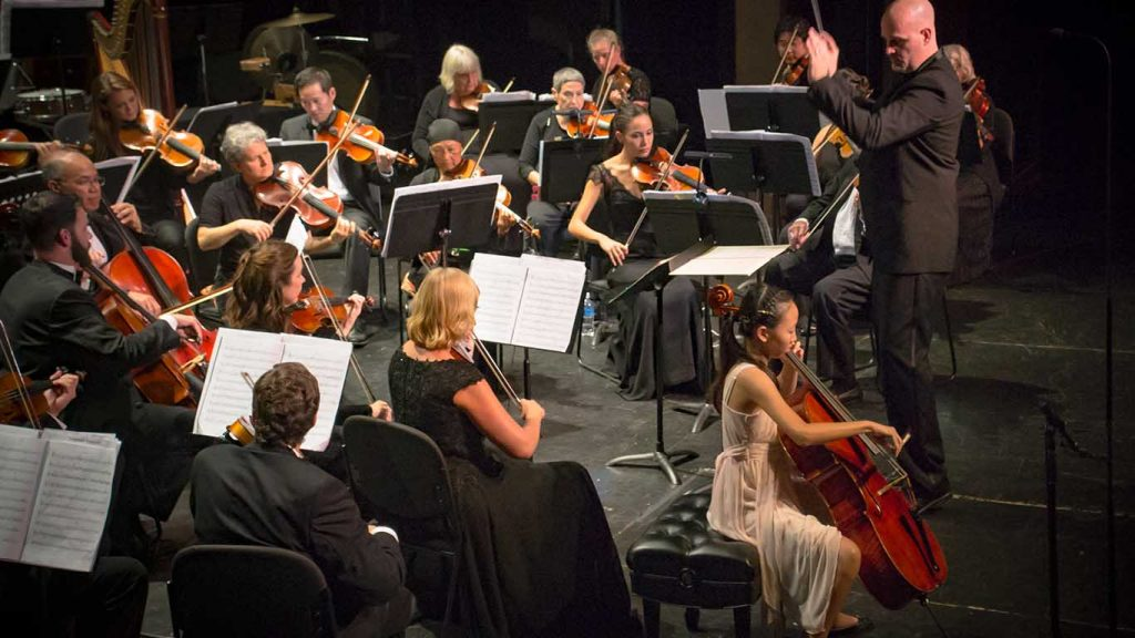 Celina Lim perfoming on cello with the Kamuela Philharmonic at Kahilu Theatre